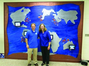 Professors John Kuiphoff '04 and Teresa Nakra stand in front of the interactive Diversity Mural they helped the students of a local grade school design and create as part of a yearlong collaboration.