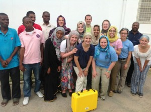 TCNJ students stand with members of Zanzibar Outreach Program and Mikunguni Youth Development Organization in Zanzibar in front of the Mnazi Mmoja Hospital, the site of their second installation of a solar-powered suitcase.